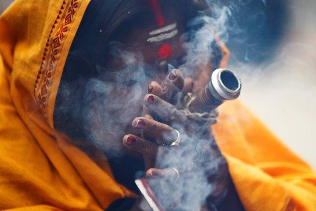 "A Hindu holy woman smokes marijuana during the ""Shivaratri"" festival at the courtyard of the Pashupatinath Hindu temple in Katmandu, Nepal, Thursday, February 27, 2014. (Photo by Niranjan Shrestha/AP Photo)"