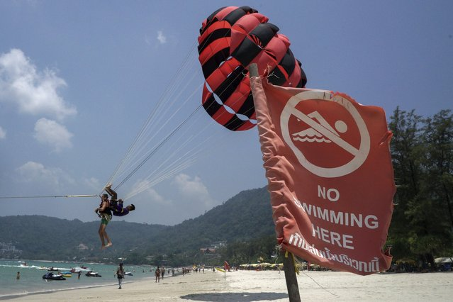 A tourist parasails at Patong beach in Phuket, Thailand March 19, 2016. (Photo by Athit Perawongmetha/Reuters)