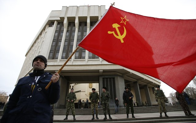 A man holds a Soviet Union flag as he attends a pro-Russian rally at the Crimean parliament building in Simferopol March 6, 2014. The decree making Crimea part of Russia is already in force and Ukrainian troops still on its territory will be treated as occupiers and forced to surrender or leave, the Russian-controlled region's deputy prime minister said. (Photo by David Mdzinarishvili/Reuters)