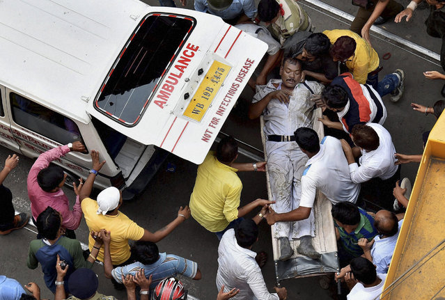 An injured traffic police officer is rushed to an ambulance after an under construction over bridge partially collapsed in Kolkata, India,Thursday, March 31, 2016. (Photo by Swapan Mahapatra/Press Trust of India via AP Photo)