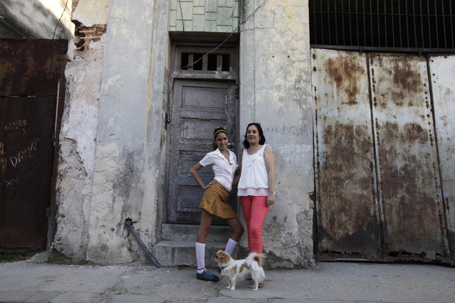 Damaris Matos Curbelo, 43, and her daughter Ana Laura Villar Matos, 14, pose for a photograph outside their home in central Havana February 12, 2014. Damaris finished her education at age 21 and works as a secretary in the office of the Historian of the City of Havana. Damaris says that when she was a child she wanted to become a doctor, and that she hopes her daughter will become a doctor. Her daughter Ana Laura says she would like to be a biologist. (Photo by Enrique De La Osa/Reuters)