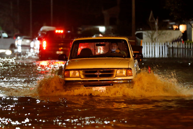 A motorist drives on a flooded street as water continues to rise after heavy rains overflowed nearby Coyote Creek in San Jose, California, U.S. February 21, 2017. (Photo by Stephen Lam/Reuters)