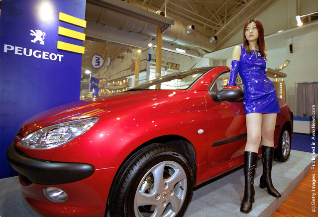 A model stands beside a French sport car in the France-China 2001 show