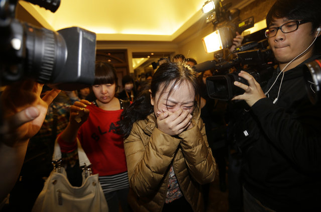 A relative (front) of a passenger of Malaysia Airlines flight MH370 cries as she walks past journalists at a hotel in Beijing March 9, 2014. (Photo by Jason Lee/Reuters)
