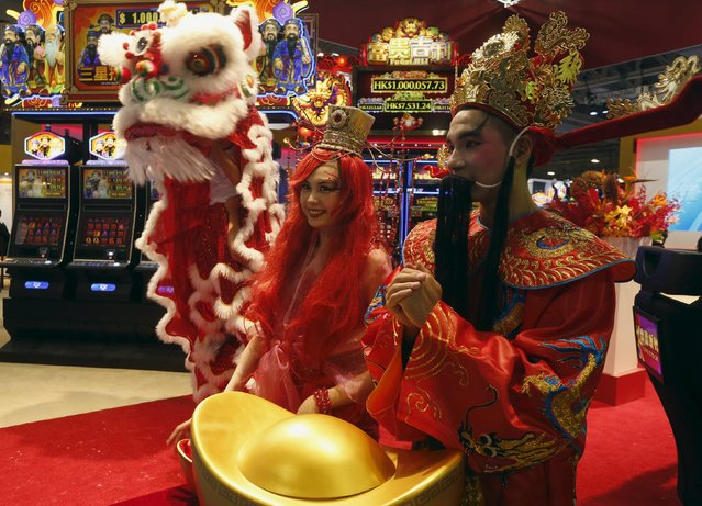 An attendant (R) dressed as the Chinese God of Wealth stands in front of slot machines at the Global Gaming Expo (G2E) Asia in Macau, China May 19, 2015. (Photo by Bobby Yip/Reuters)