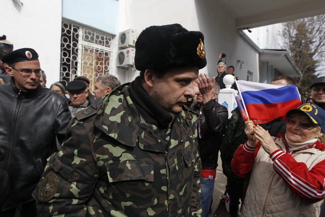 A Ukrainian serviceman (C) passes by pro-Russian supporters and members of self-defence units as he leaves the naval headquarters in Sevastopol, March 19, 2014. Three Russian flags were flying at an entrance to Ukraine's naval headquarters in the Crimean port of Sevastopol on Wednesday, witnesses said, as pro-Russian forces took control of at least some of the base without armed resistance. (Photo by Vasily Fedosenko/Reuters)