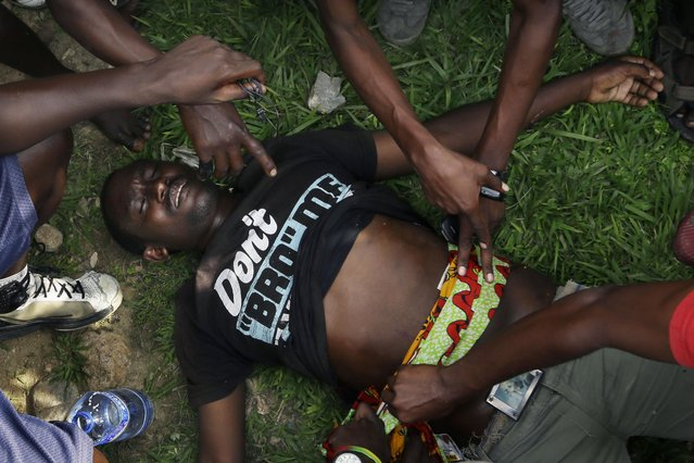 A man suffering from a bullet wound to the stomach says waiting for an ambulance in the Musaga neighborhood of Bujumbura, Burundi, Thursday May 21, 2015. Protests continue against the  President's decision to seek a third term. (Photo by Jerome Delay/AP Photo)