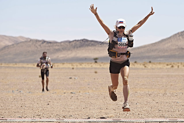 Russian Natalia Sedykh celebrates after crossing the finish line during the last stage of the 31st edition of the Marathon des Sables between Hassi Tarfa and Bou Makhlouf in the southern Moroccan Sahara desert on April 15, 2016. The 31st edition of the marathon is a live stage 257 kilometre race through a formidable landscape in one of the world's most inhospitable climates. (Photo by Jean-Philippe Ksiazek/AFP Photo)