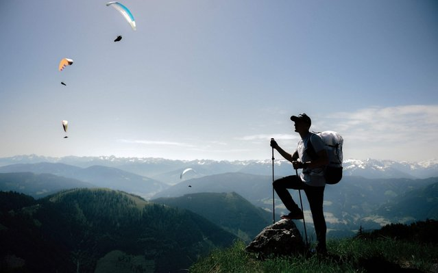 French athlete Benoit Outters looks at paragliders flying during a training session prior the Red Bull X-Alps race on June 14, 2019 in Bergbahnen Werfenweng, western Austria. The race start in Wagrain, Austria crossing the borders of six countries covering more than 1,138km of alpine terrain only on foot and paragliding, and arrive in Monaco, France. (Photo by Lucas Barioulet/AFP Photo)
