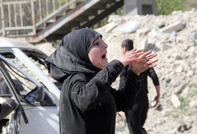 A women reacts following a reported air strike by government forces on April 2, 2014, in the Sakhur neighborhood in the northern Syrian city of Aleppo. More than 150,000 people have been killed in Syria since the conflict began in March 2011, the Syrian Observatory for Human Rights said in a new toll released. (Photo by Mohammed Al-Khatieb/AFP Photo)