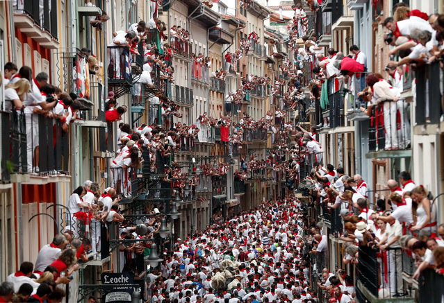 Runners try to avoid bulls as they run down a street during the traditional San Fermin bull run in Pamplona, Spain, 07 July 2019. The festival, locally known as Sanfermines, is held annually from 06 to 14 July in commemoration of the city's patron saint. Hundreds of thousands of visitors from all over the world attend the fiesta, with many of them physically participating in the highlight event – the running of the bulls, or encierro. (Photo by Villar Lopez/EPA/EFE)