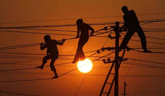 In this Thursday, December 30, 2010 file photo, workers repair electrical wires along the banks of the Ganges River in Allahabad, India. (Photo by Rajesh Kumar Singh/AP Photo)