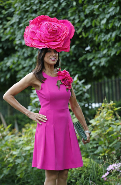 A race goer poses for photographers on the second day of  Royal Ascot horse racing meet at Ascot, England, Wednesday, June 17, 2015. Royal Ascot is the annual five day horse race meeting that Britain's Queen Elizabeth II attends every day of the event.(AP Photo/Alastair Grant)