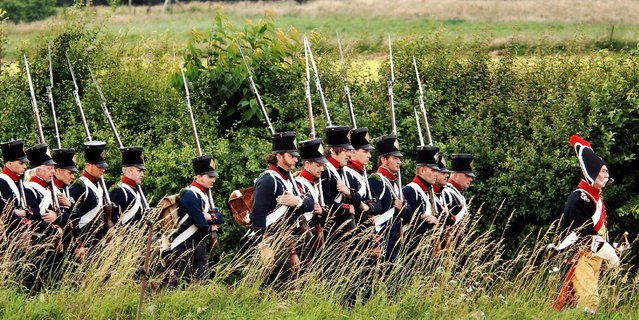 In this June 16, 2007,  file photo, actors play the part of soldiers during a re-enactment of the Battle of Waterloo in Braine-l'Alleud, near Waterloo, Belgium. The Battle of Waterloo, fought on June 18, 1815, was Napoleon Bonaparte's last battle, as his defeat put a final end to his rule as Emperor of France. (AP Photo/Geert Vanden Wijngaert, File)