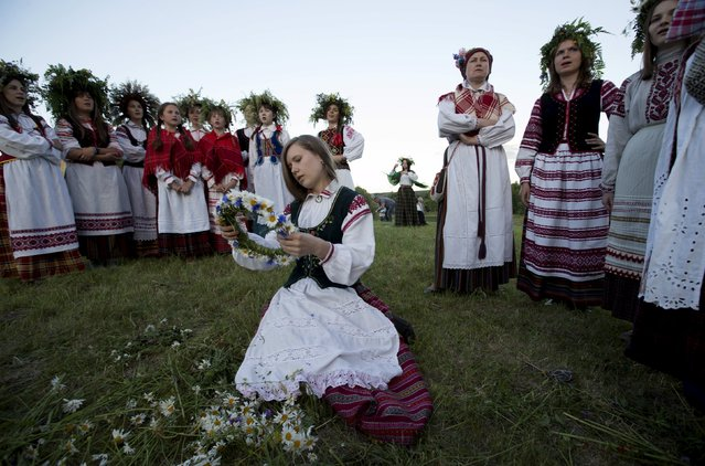 Belarusian women and girls make wreaths and sing songs as they take part in the Ivan Kupala festival near the town of Rakov, west of Minsk June 27, 2015. (Photo by Vasily Fedosenko/Reuters)