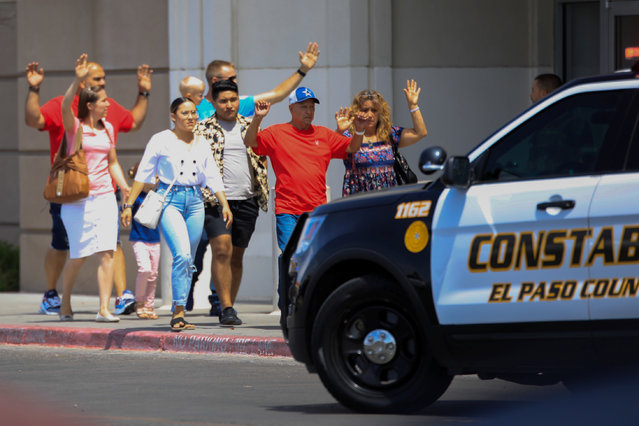 Shoppers exit with their hands up after a mass shooting at a Walmart in El Paso, Texas, U.S. on August 3, 2019.  Multiple people were killed and one person was in custody after a shooter went on a rampage at a shopping mall, police in the Texas border town of El Paso said. (Photo by Jorge Salgado/Reuters)