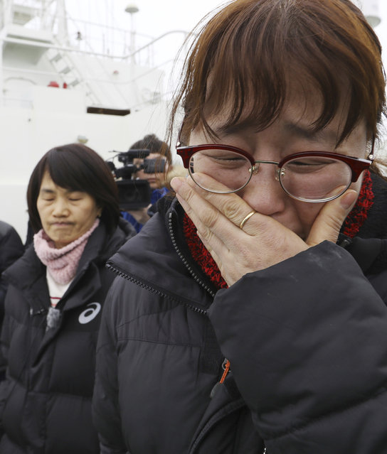 A relative of missing passengers of the sunken Sewol ferry cries as she watches workers lifting the boat in waters off Jindo, South Korea, Thursday, March 23, 2017. South Korean workers on Thursday slowly pulled up the 6,800-ton ferry from the water, nearly three years after it capsized and sank into the violent seas off South Korea's southwestern coast, an emotional moment for a country that continues to search for closure to one of its deadliest disasters ever. (Photo by Lee Jin-wook/Yonhap via AP Photo)