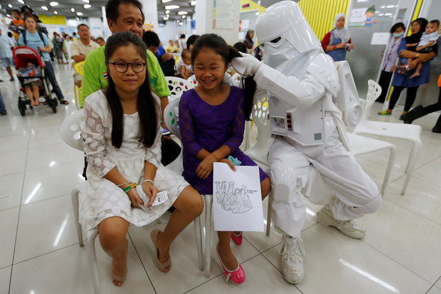 A member of a Star Wars fan club in Thailand, dressed as a Snowtrooper plays with children during Star Wars Day celebration at the Queen Sirikit National Institute of Child Health in Bangkok, Thailand, May 4, 2016. (Photo by Chaiwat Subprasom/Reuters)
