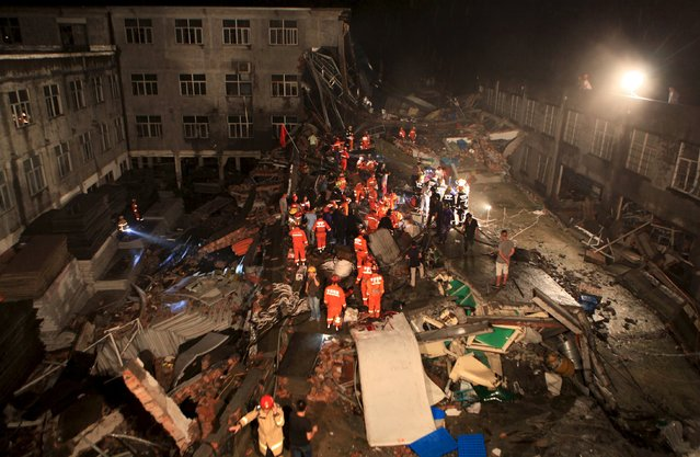 Rescue workers search at the site after a shoe factory building collapsed in Wenling, Zhejiang province, July 4, 2015. The accident killed at least 11 people and injuried 33, according to local media. (Photo by Reuters/Stringer)
