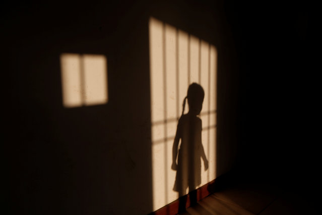 The niece of Maroly Bastardo, an eight months pregnant woman who, along with her children, her husband's sister, uncle and father, disappeared in the Caribbean Sea after boarding a smuggler's boat during an attempt to cross from Venezuela to Trinidad and Tobago, casts her shadow at her relatives' home in El Tigre, Venezuela, June 3, 2019. (Photo by Ivan Alvarado/Reuters)