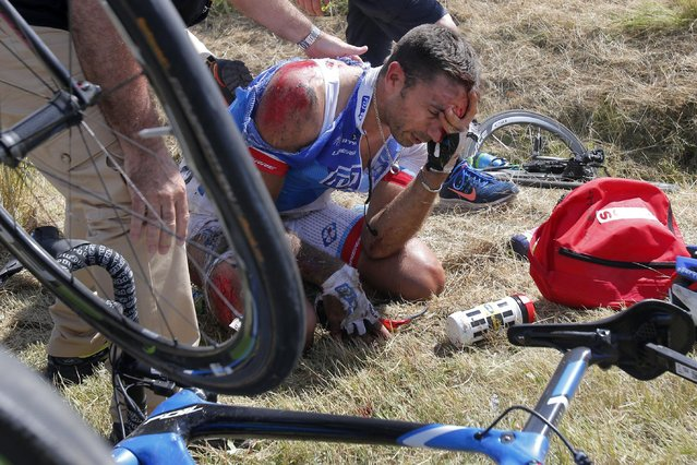William Bonnet of France holds his head after crashing with scores of other riders during the third stage of the Tour de France cycling race over 159.5 kilometers (99.1 miles) with start in Antwerp and finish in Huy, Belgium, Monday, July 6, 2015. (Photo by Christophe Ena/AP Photo)