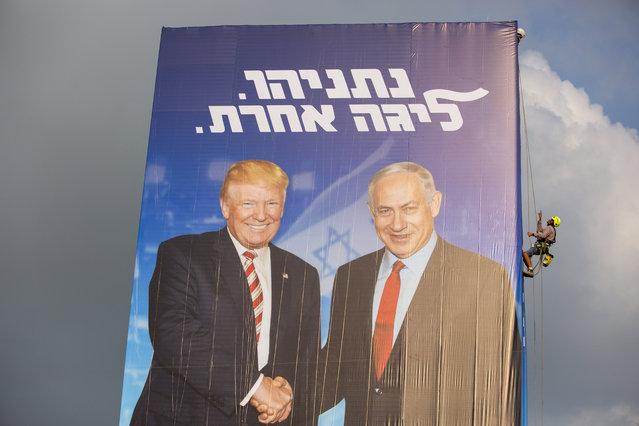 """A worker hangs an election campaign billboard of the Likud party shows Israeli Prime Minister Benjamin Netanyahu, right, and US President Donald Trump in Bnei Brak, Israel, Sunday, September 8, 2019. Hebrew on the billboard reads """"Netanyahu, in another league"""". (Photo by Oded Balilty/AP Photo)"""