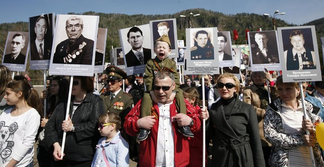 People carrying portraits of deceased relatives who took part in World War Two, march in a parade during Victory Day commemorations in the town of Divnogorsk, near Russia's Siberian city of Krasnoyarsk, May 9, 2014. Russia celebrates the 69th anniversary of the victory over Nazi Germany on Friday. (Photo by Ilya Naymushin/Reuters)