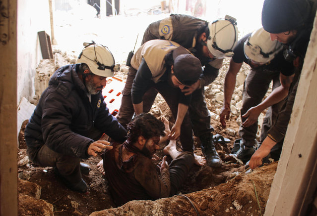 Members of the Syrian civil defence volunteers, also known as the White Helmets, remove a victim from the rubble of his house on April 8, 2017, following a reported air strike by government forces on a rebel- held area in the southern Syrian city of Daraa. (Photo by Mohamad Abazeed/AFP Photo)
