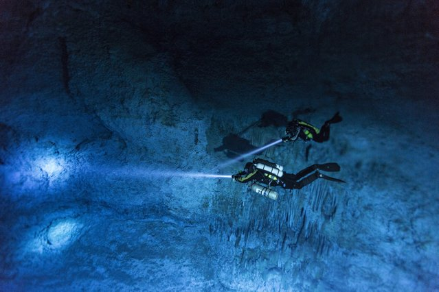 Divers Susan Bird and Alberto Nava search the walls of Hoyo Negro, an underwater cave on Mexico's Yucatan Peninsula, where the remains of a 12,000- to 13,000-year-old teenage girl, were found in 2007 in this handout photo provided by National Geographic on May 15, 2014. (Photo by Paul Nicklen/Reuters/National Geographic)