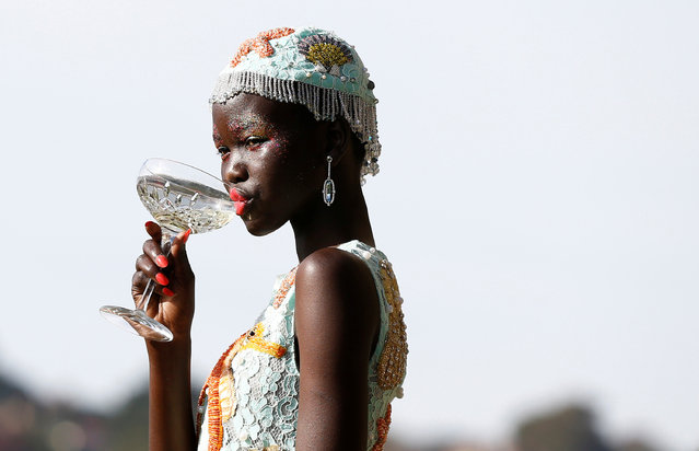 A model takes a sip of her drink during a fashion show for the label Romance Was Born on the waterfront of Sydney Harbour during Australian Fashion Week, Sydney, Australia May 18, 2016. (Photo by Jason Reed/Reuters)
