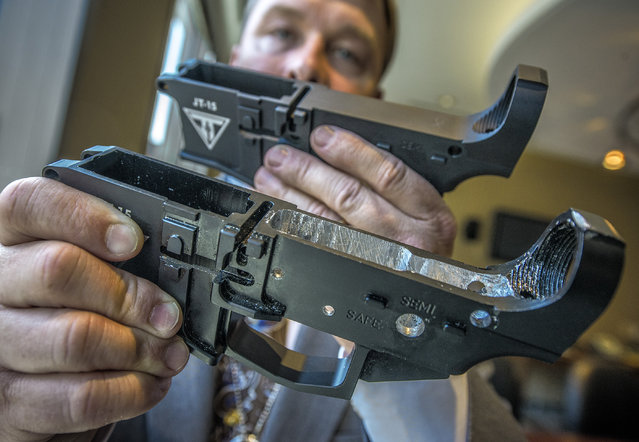 An ATF agent holds a generic unfinished receiver, back, and one that has been machined, front, at an ATF field office, on May, 06, 2014 in Washington, DC. Unfinished receivers can be turned into working automatic weapons that are untraceable. (Photo by Bill O'Leary/The Washington Post)