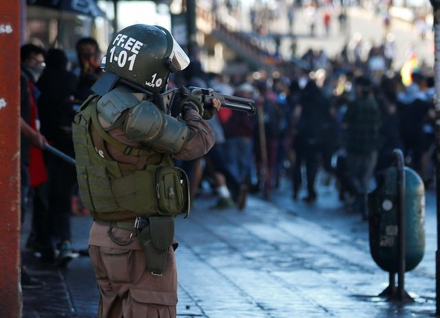 A member of the security forces aims his weapon during a protest against Chile's government in Valparaiso, Chile on October 28, 2019. (Photo by Rodrigo Garrido/Reuters)