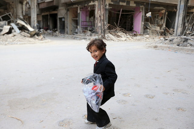 A boy carries a bag of new clothes ahead of the Eid al-Fitr holiday marking the end of Ramadan in Jobar, a suburb of Damascus, Syria July 15, 2015. (Photo by Bassam Khabieh/Reuters)