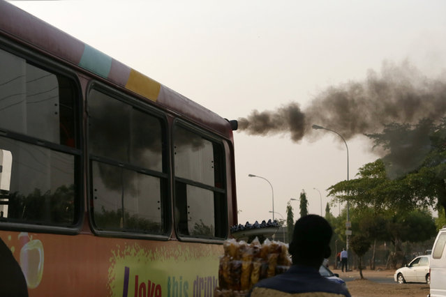 A man sells plantain chips near a bus with smoke seen from its exhaust at a bus park in Abuja, Nigeria, February 1, 2017. (Photo by Afolabi Sotunde/Reuters)