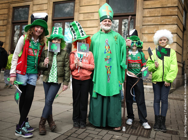 Children stand with a man dressed as St Patrick before taking part in a St Patrick's day parade on March 18, 2012 in London