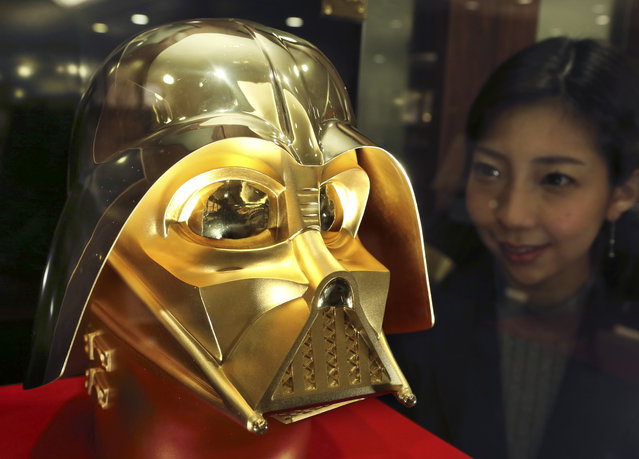 Tokyo gold jeweler Ginza Tanaka employee Momoko Marutani looks at the gold mask of Darth Vader at the jewelry shop in Tokyo, Monday, May 1, 2017. The life-size mask of Star Wars villain Darth Vader will be up for sale for a hefty price of 154 million yen ($1.38 million). The 24-karat mask was created by the gold jeweler to mark the 40th anniversary since the release of the first Star Wars film. (Photo by Koji Sasahara/AP Photo)