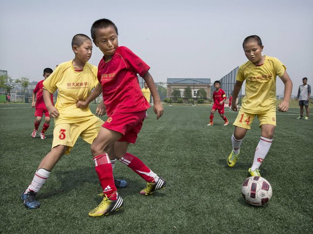 Students play during a match on a practice pitch at the Evergrande International Football School near Qingyuan in Guangdong Province. (Photo by Kevin Frayer/Getty Images)
