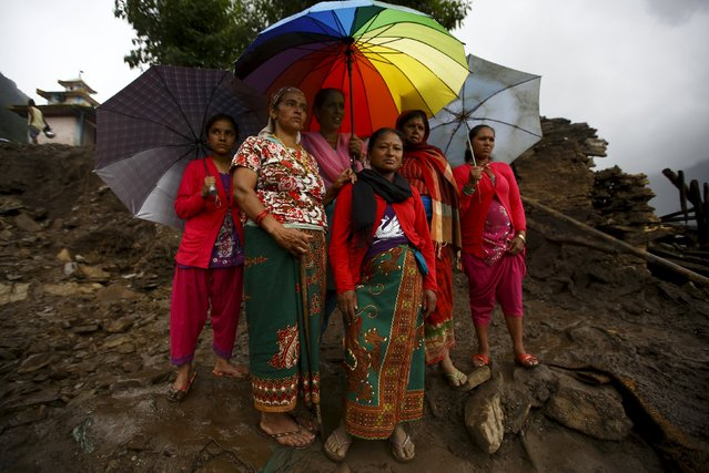 Villagers watch as rescue teams search for missing people after the landslide at Lumle village in Kaski district July 30, 2015. (Photo by Navesh Chitrakar/Reuters)