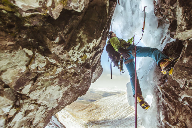 """Winter Climbing from inside Ben Nevis"". The view from inside the mountain, as a winter climber passes through the cave on Minus Three gully. Photo location: Ben Nevis, Fort William, Scotland. (Photo and caption by Daniel Wildey/National Geographic Photo Contest)"
