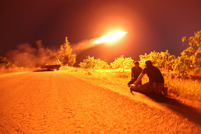 Syrian fighters from the Turkish-backed National Liberation Front (NLF) fire a missile against regime positions on May 13, 2019 in the rebel-held northern part of Syria's Hama province. Clashes on the edge of a jihadist bastion in northwestern Syria have killed at least 42 fighters in 24 hours, a monitor said today, after regime bombardment on the region devastated health services. (Photo by Omar Haj Kadour/AFP Photo)