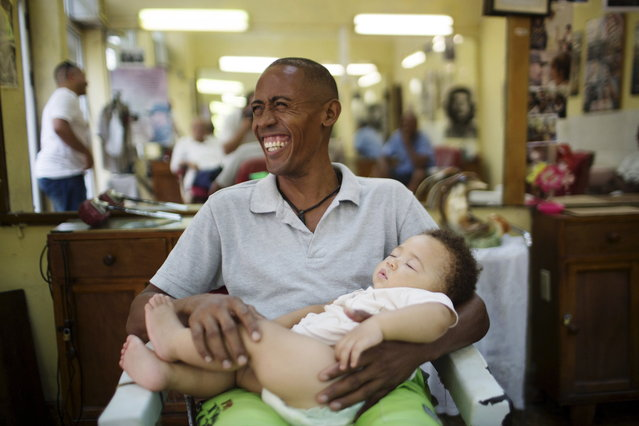 Street vendor Alain Rivera, 37, holds his 10-month-old nephew in a barber shop in downtown Havana, July 14, 2015. (Photo by Alexandre Meneghini/Reuters)