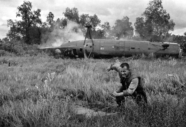 A U.S. crewman runs from a crashed CH-21 Shawnee troop helicopter near the village of Ca Mau in the southern tip of South Vietnam, Dec. 11, 1962