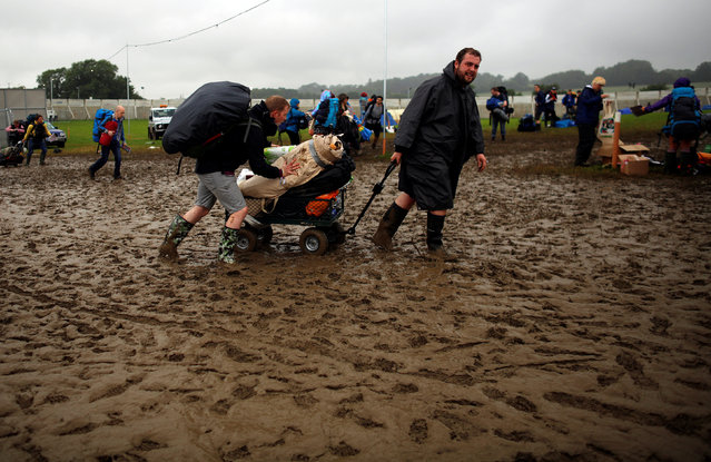 Revellers transport a cart with their belongings as they arrive at Worthy Farm in Somerset for the Glastonbury Festival, Britain June 22, 2016. (Photo by Stoyan Nenov/Reuters)