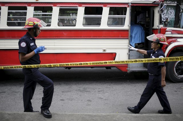 Paramedics are seen outside a public bus, where its driver and his assistant (background, covered with blue sheet) were shot dead, in Mixco, on the outskirts of Guatemala City, August 11, 2015. (Photo by Jorge Dan Lopez/Reuters)