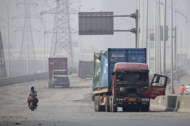 Motorcyclists ride along a highway, next to damaged trucks, near the site of the explosions at the Binhai new district in Tianjin August 13, 2015. (Photo by Jason Lee/Reuters)