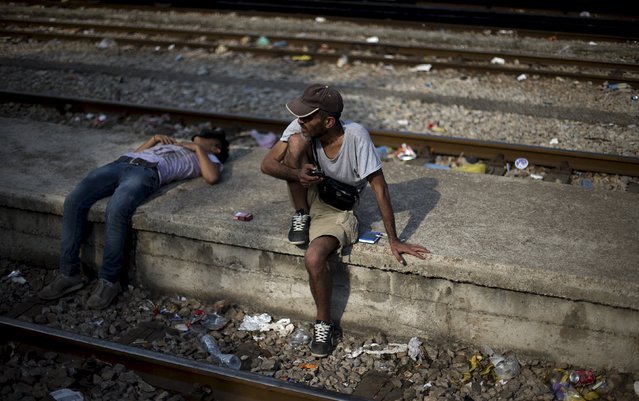 Migrants rest as they wait for a train to arrive at Gevgelija train station in Macedonia, close to the border with Greece, August 14, 2015. (Photo by Stoyan Nenov/Reuters)