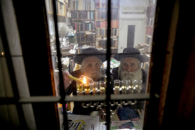 "Ultra-Orthodox Jews light a Hanukkah candle inside their house during the Jewish holiday of Hanukkah in the Mea Shearim neighbourhood of Jerusalem, Israel, 23 December 2019. Hanukkah, also known as the ""Festival of Lights"", is one of the most important Jewish holidays and is celebrated by Jews worldwide. This year, Hanukkah began in the evening of 22 December 2019 and ends in the evening of 30 December 2019. (Photo by Abir Sultan/EPA/EFE)"
