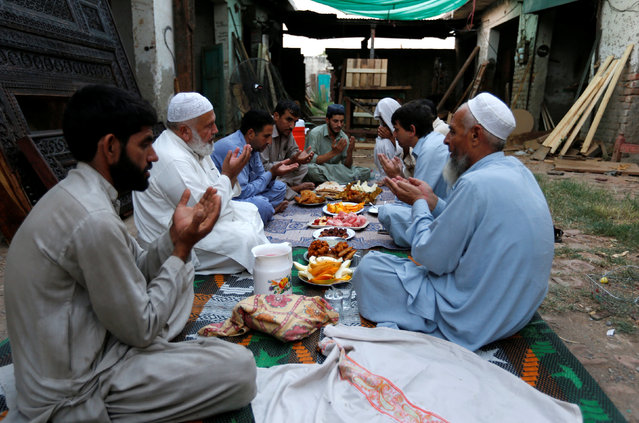 Workers and neighbours of a carpentry workshop pray before breaking fast during the holy month of Ramadan in Islamabad, Pakistan June 11, 2016. (Photo by Caren Firouz/Reuters)