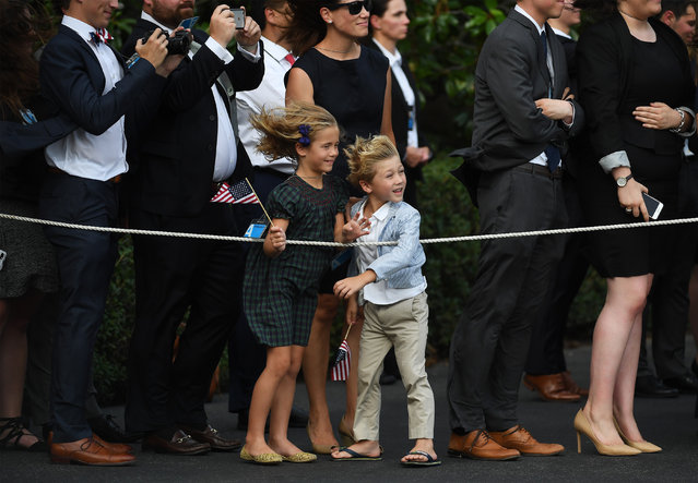 Children watch President Donald Trump and First Lady Melania Trump leave Marine One from the White House for a trip in France on Wednesday July 12, 2017 in Washington, DC. (Photo by Matt McClain/The Washington Post)