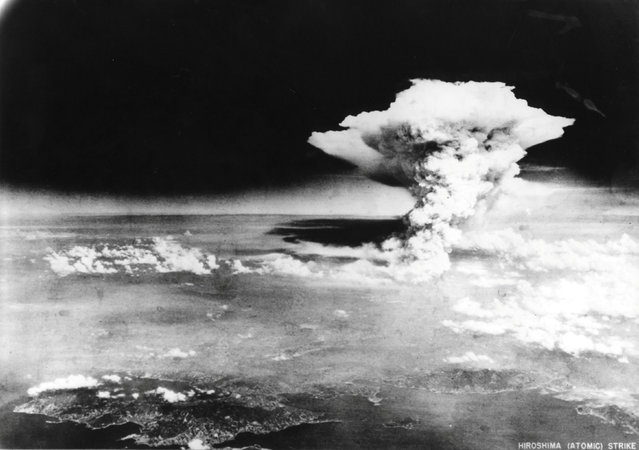 An atomic cloud billows, following the explosion of the first atomic bomb to be used in warfare in Hiroshima, Japan, in this handout photo taken by U.A. Army on August 6, 1945, and distributed by the Hiroshima Peace Memorial Museum. The word written on the photo are from source. (Photo by Reuters/U.S. Army/Hiroshima Peace Memorial Museum)